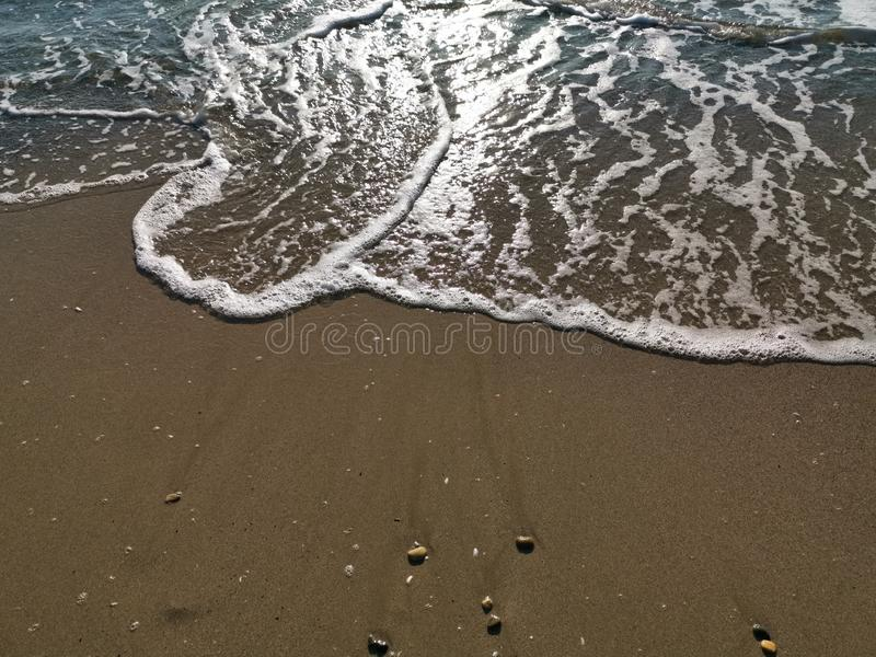Wave on the sand beach. Sand with scraps of shells and the wave that broke at the shore in the sunlight stock image