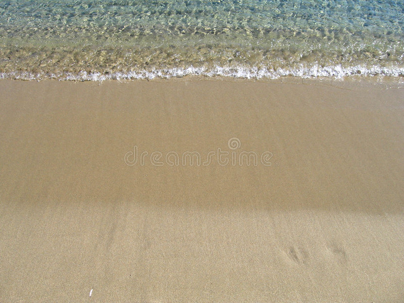 Wave on a sandy beach, on summer vacations stock photos