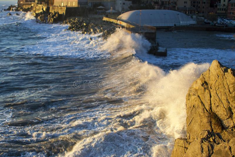 A wave of several meters crashes on a small port royalty free stock image