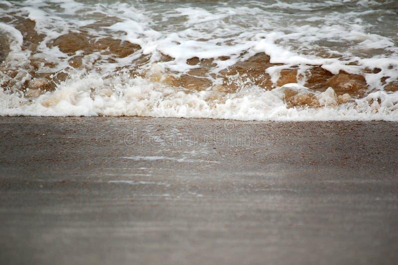 Wave splash on sand royalty free stock photography