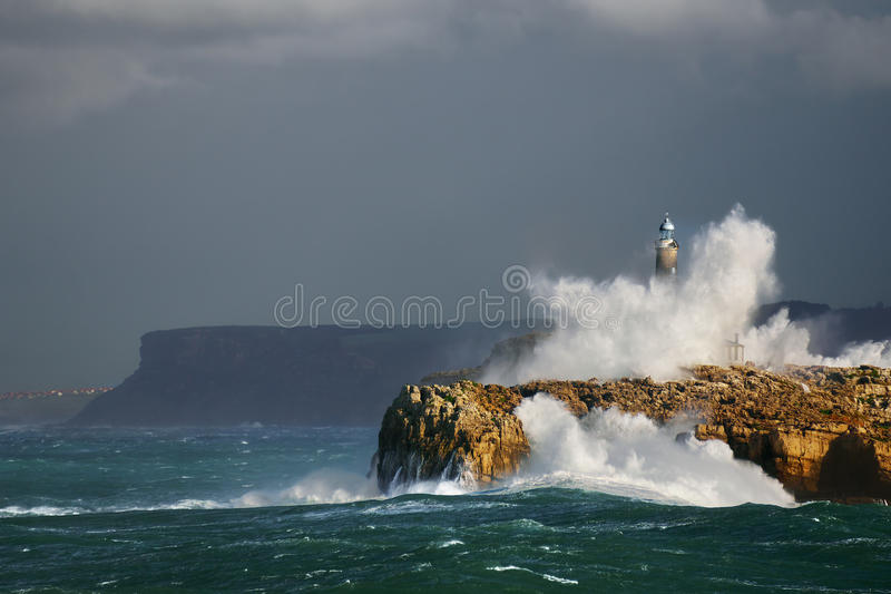 Wave splashing in Mouro lighthouse in Santander stock photography