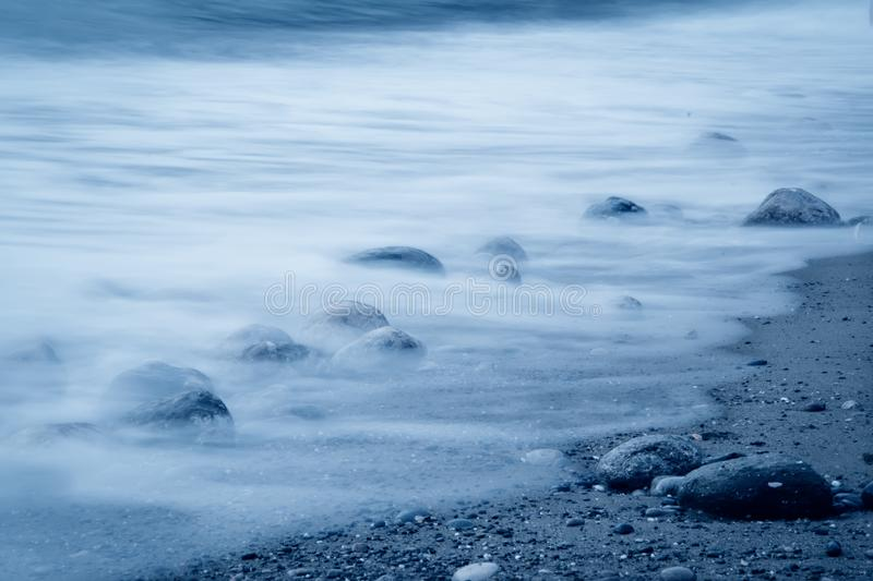 Wave surf. Stones on the seashore in a trendy classic blue tone. Wave surf. Stones on the seashore. Classic Blue color 2020 stock image