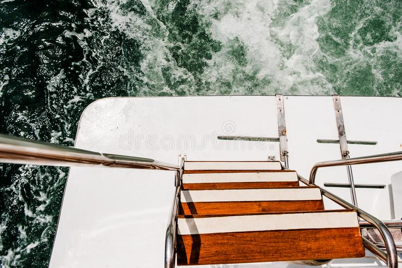 Wave trace on sea water surface behind of fast moving power boat. Rear swim platform of boat stock photos