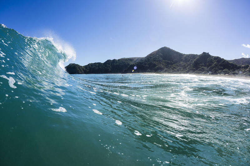 Wave Tubing, North Piha, New Zealand. A water shot taken as a wave creates a perfect tube at North Piha Beach, New Zealand stock photo