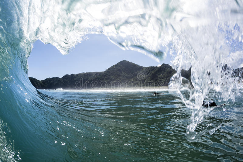 Wave Tubing, North Piha, New Zealand. A water shot taken as a wave creates a perfect tube at North Piha Beach, New Zealand stock image