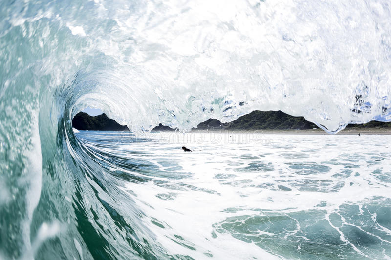 Wave Tubing, North Piha, New Zealand. A water shot taken as a wave creates a perfect tube at North Piha Beach, New Zealand royalty free stock photography