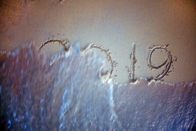 Wave Washing Away 2019 Year Handwritten On Sandy Beach royalty free stock photo