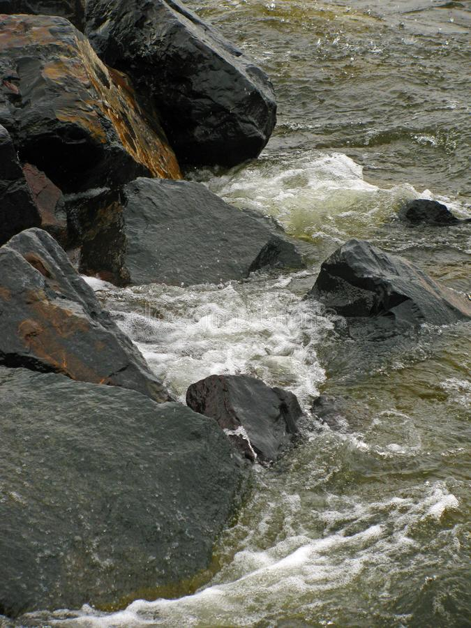 Waves against rocks in Duluth royalty free stock photo
