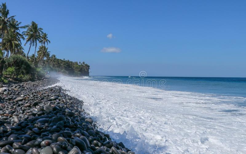 Waves attack the stony beach, and sea water spills over the beach`s edge. Palm trees and tropical vegetation line the coast of the. Indian Ocean off Bali Island stock images