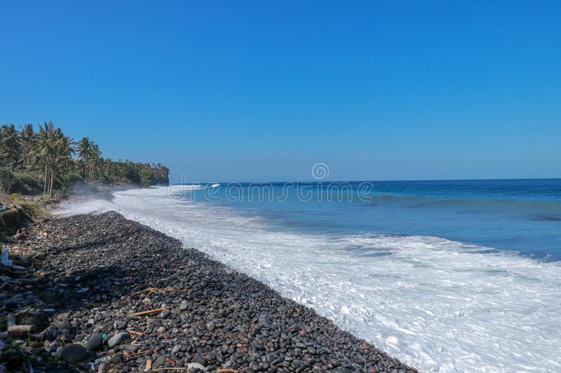 Waves attack the stony beach, and sea water spills over the beach`s edge. Palm trees and tropical vegetation line the coast stock image