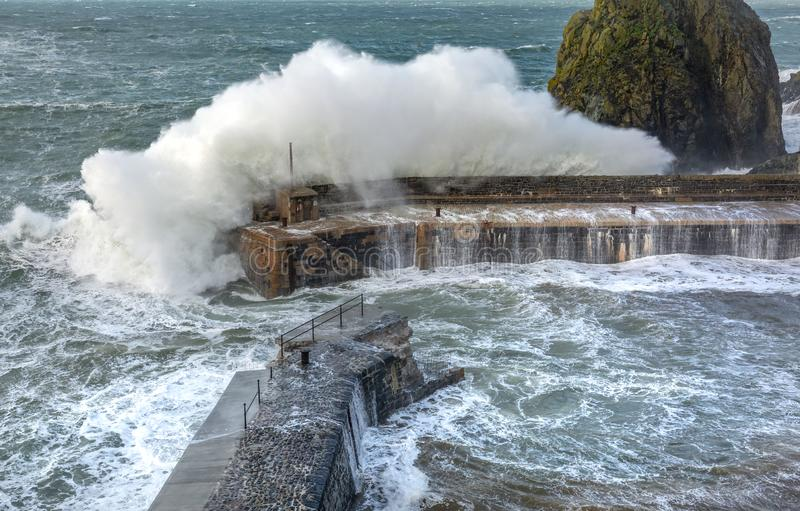 Waves batter the harbour, Mullion Cove, Cornwall royalty free stock image