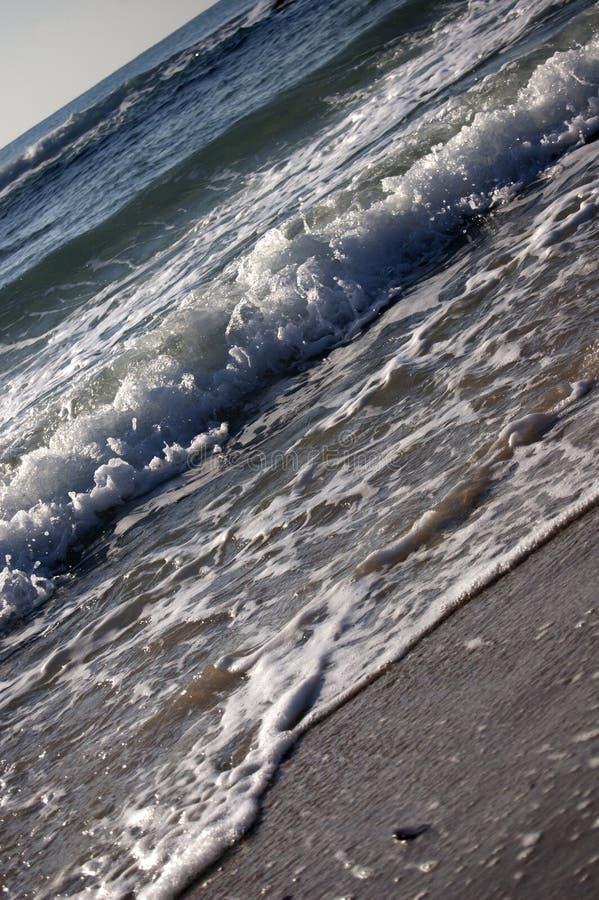 Waves on a beach royalty free stock photos