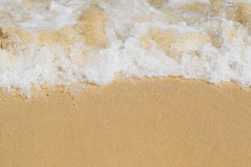 Close-up of foamy waves breaking on a beach. Close up shot of waves breaking on a beach in the sunshine stock photography
