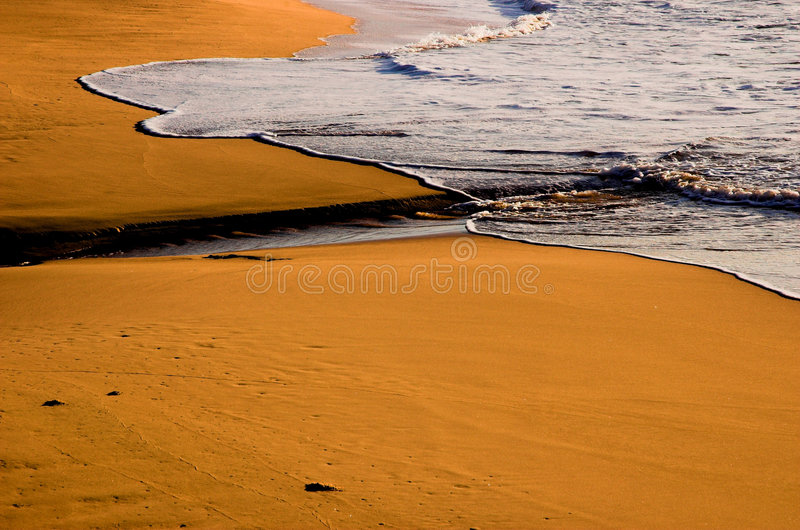 Waves and beach at dawn. Waves and red beach sand at dawn royalty free stock photography