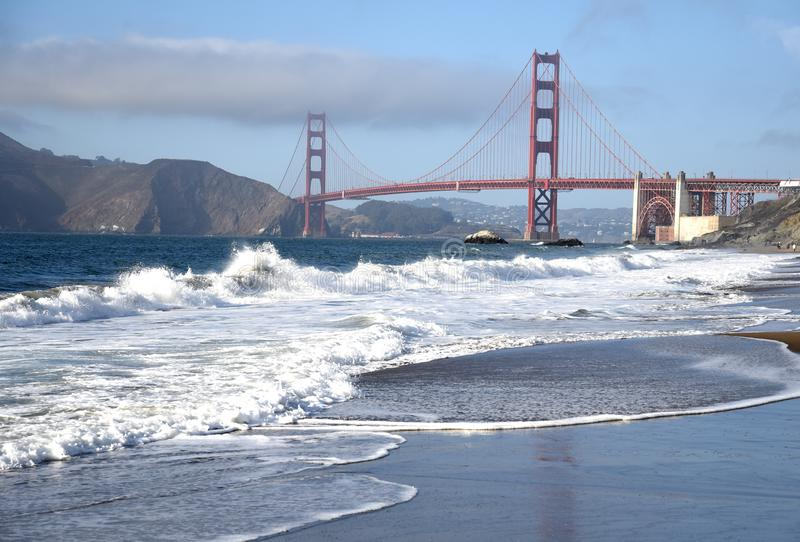 Waves on the beach with the golden gate stock photography