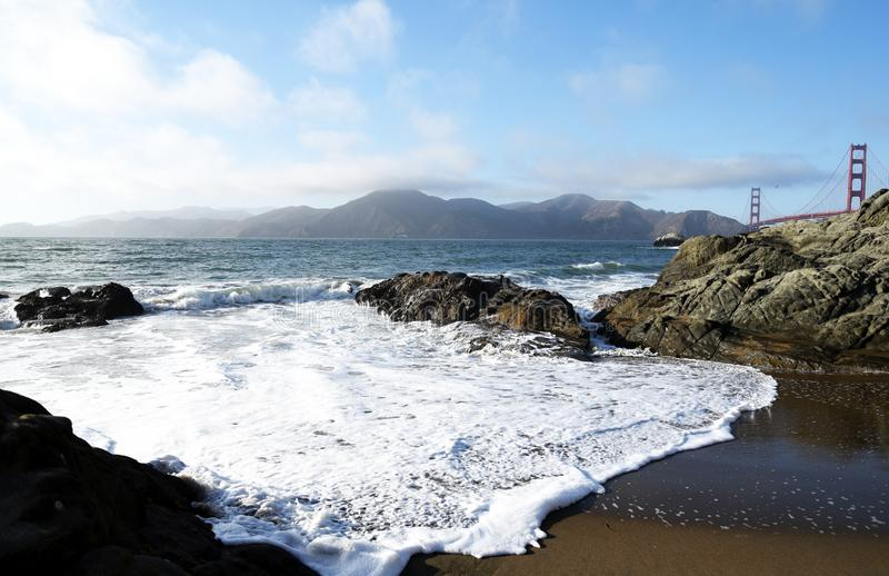 Waves on the beach by the golden gate bridge royalty free stock photography