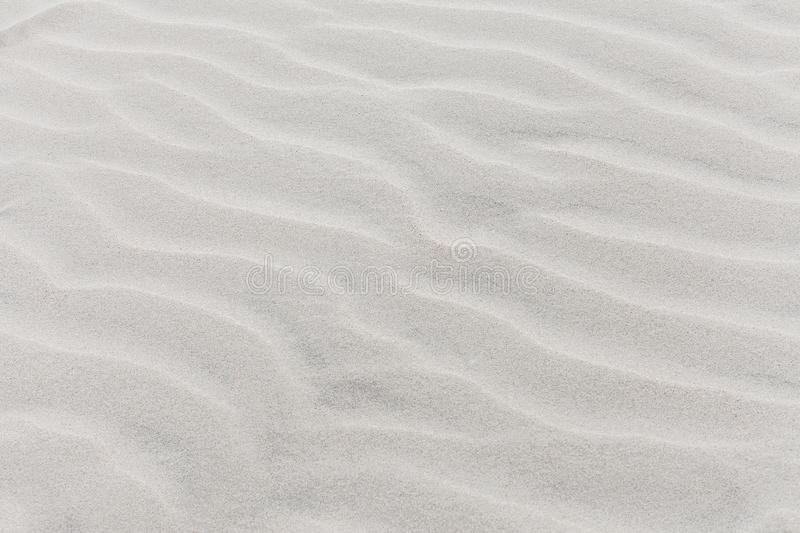 Waves on beach of gray sand. Textural background stock images