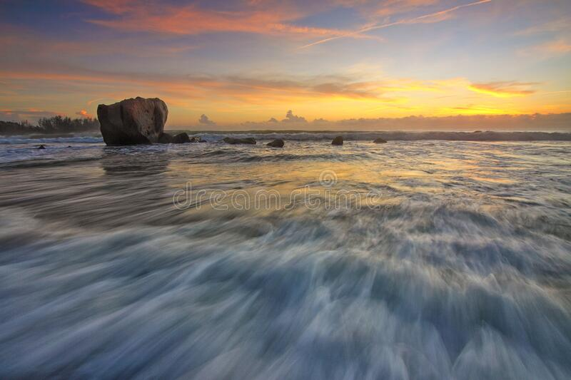 Waves on beach with rock at sunset royalty free stock photo