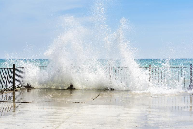 Waves beat against old pier stones on a sunny day. A lot of splashes royalty free stock image