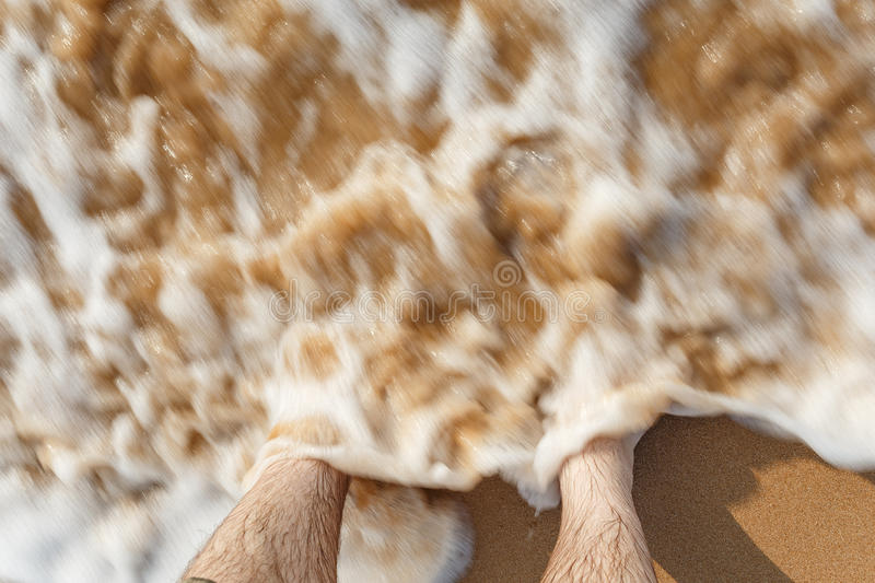 Waves beating against legs on the beach. Ocean waves beating against legs on the beach royalty free stock images