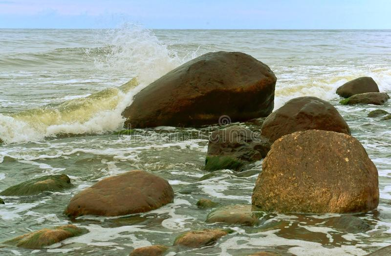 The waves are beating on the coastal boulders, the sea wave breaks on the rocks stock images