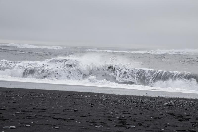 Waves in the beautiful volcanic black sand beach. royalty free stock photo