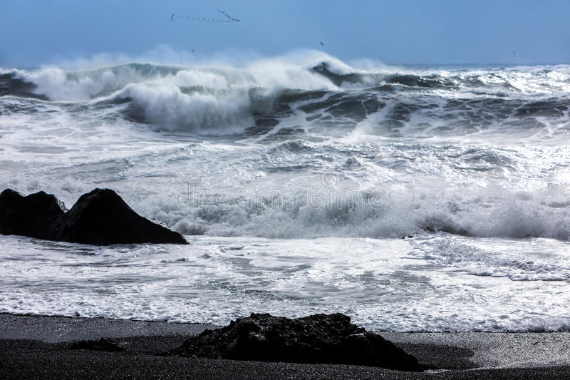 Waves on the black beach of Reynisfjara in Iceland. Turbulent waves that crash with great power on the black beach of Reynisfjara in the area of Vik in Iceland royalty free stock photos