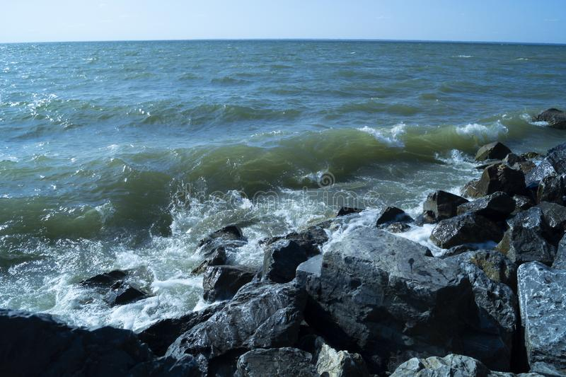 Waves of blue seas are found on rocks and crash into them. Forming a spray royalty free stock photography