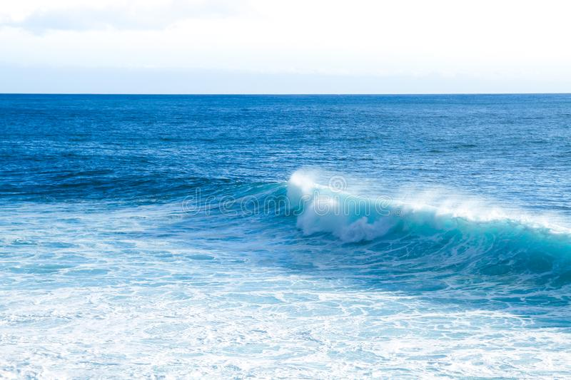 Waves braking close to the beach shore with blue turquoise ocean water and resulting white foam stock photography