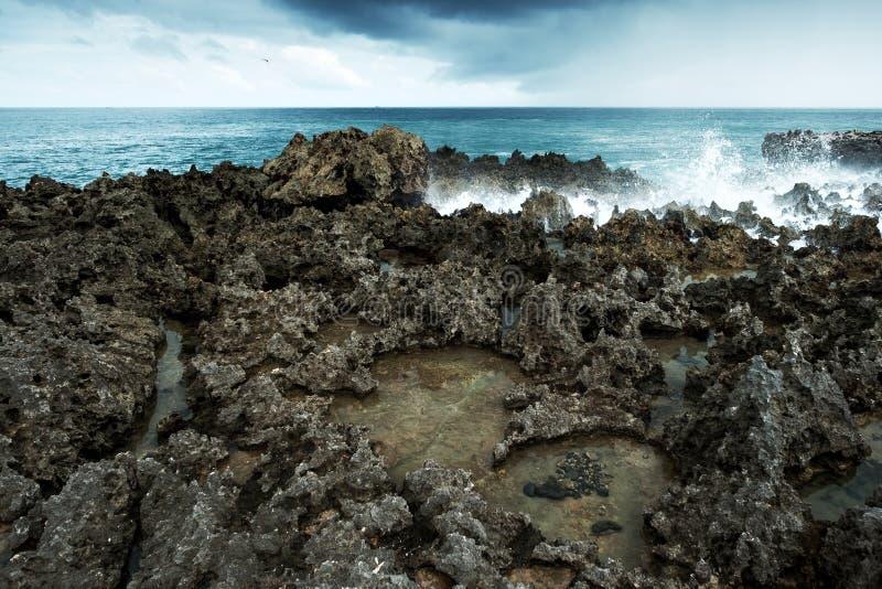 Waves break on rocky shore. Tourist beach resort in Nuca Dua of Bali stock images