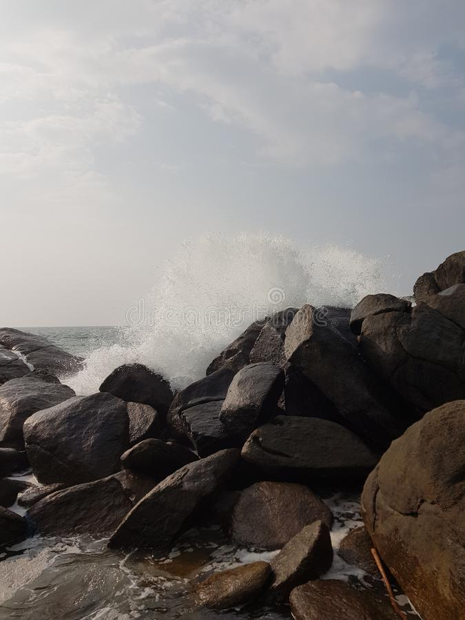 Waves breaking on the beach stones. Spray flying in all directions royalty free stock image