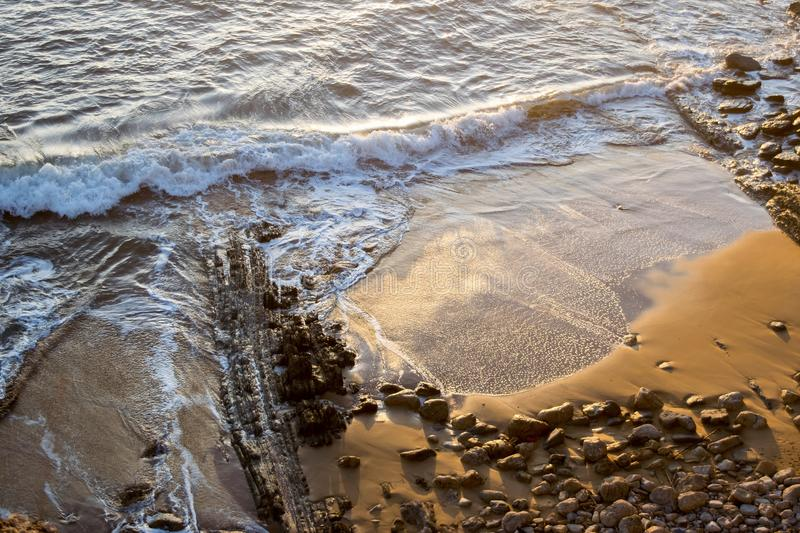 Waves breaking on the beach. At sunset stock image