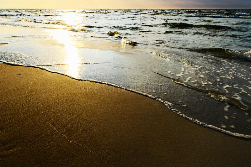 Waves breaking on the beach at sunset. Baltic sea, Pomerania, northern Poland royalty free stock photography