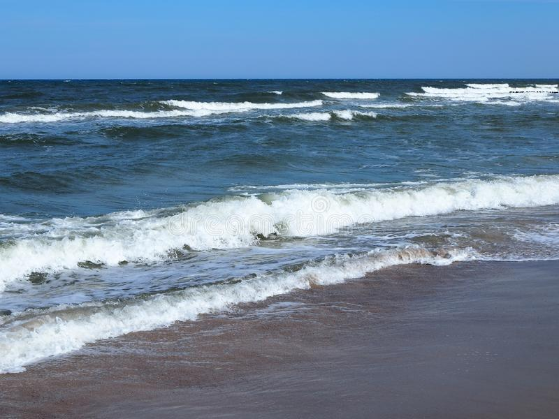 Waves breaking on beach. Wind, sun and sea on one day royalty free stock image