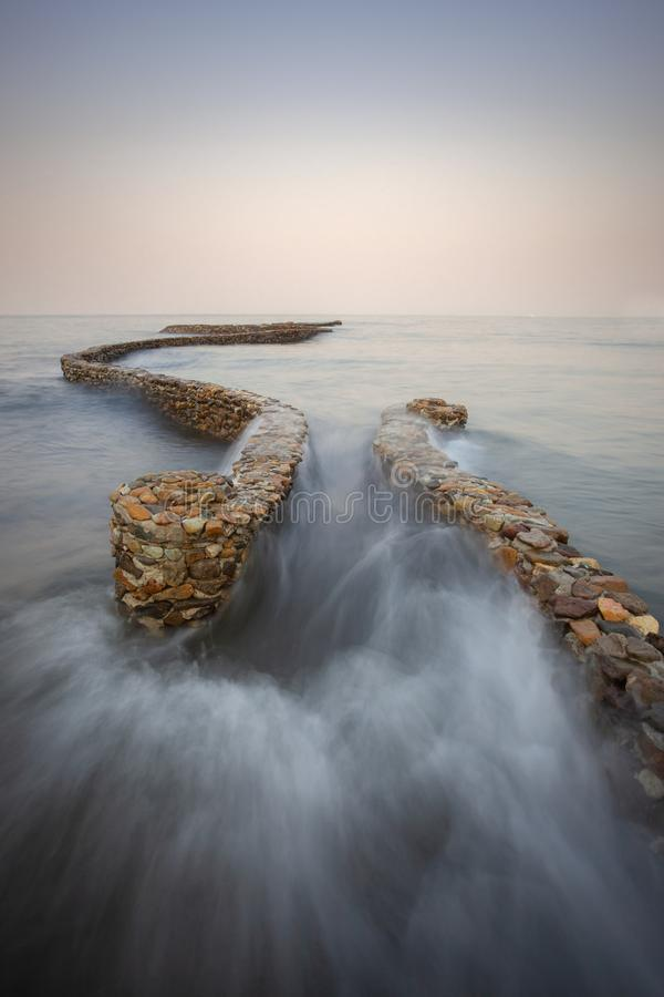 Waves breaking on the breakwater stock photo