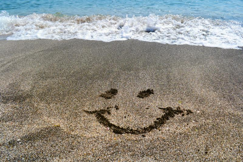 Waves Breaking Down on the Sea Shore and Smile in the Sand. Shore Line , Waves with Foam and smiley face in the sand royalty free stock photos