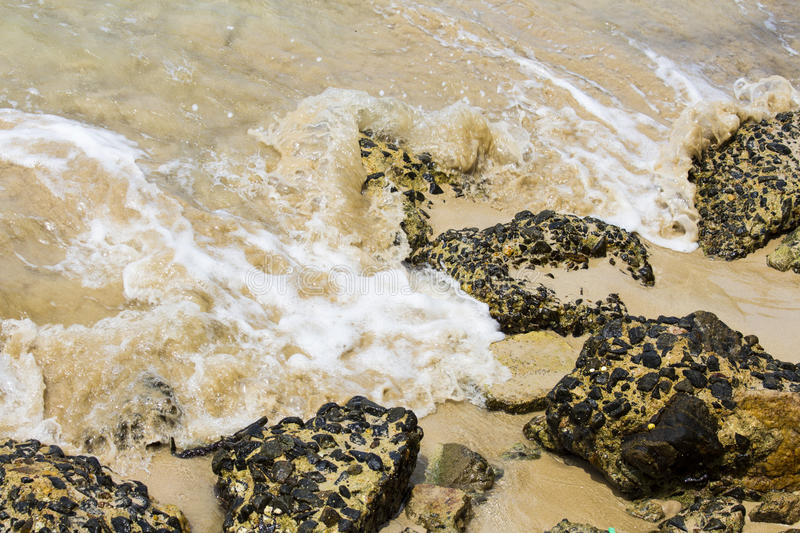 Waves breaking on giant rocks stock photography