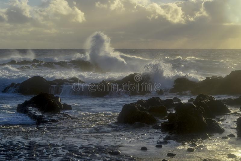 Waves breaking through lava rocks at sunset on the island stock image