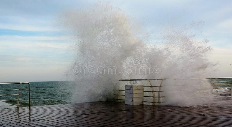 The waves breaking on a mooring , forming a spray. Waves break sea embankment in storm. royalty free stock image