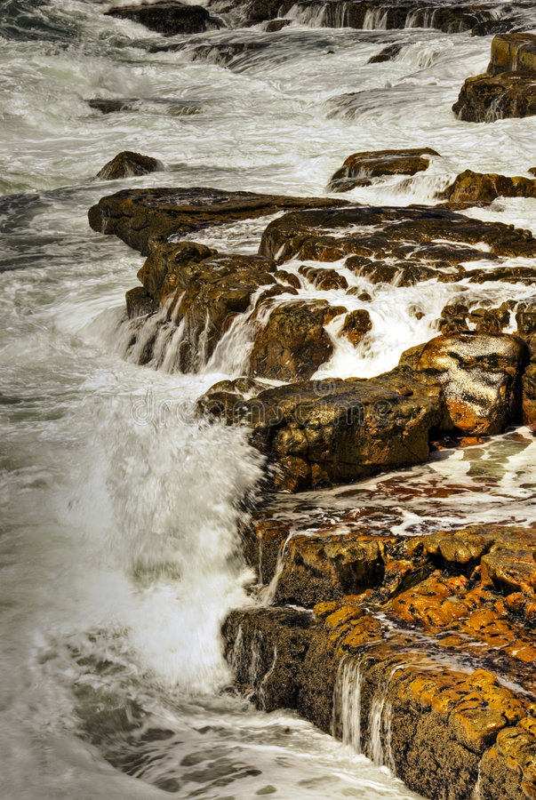 Waves breaking on rocks. A view looking along a rocky coastline as relentless ocean waves break over them stock photography