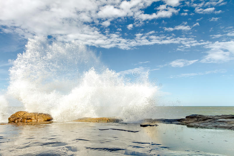 Waves breaking on the rocks at sunset on a beach. In Mar del Plata, Argentina royalty free stock photography