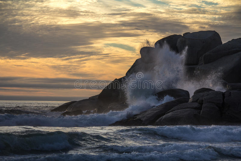 Waves breaking on rocky shore stock photo