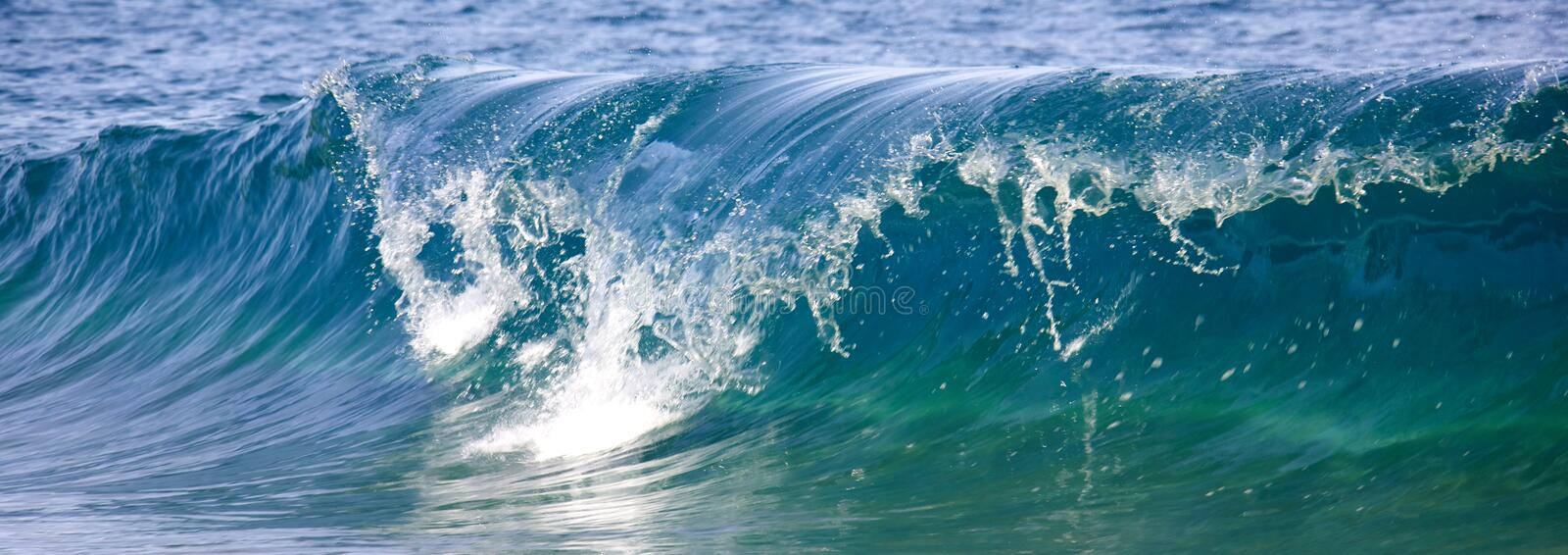 Waves breaking on the shore stock images