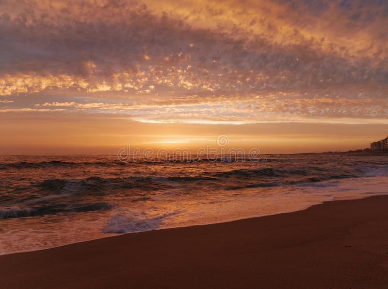 Waves breaking on shore at sunset on beach with beautiful orange sky. In Portugal during summer stock image