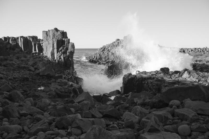Waves breaking on stones, Bombo, NSW stock photography