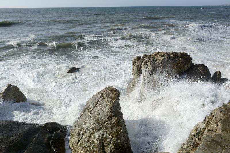 Furious Waves on the Rocks. Waves bustling furiously on rocks with lots of foam and splashes stock photo