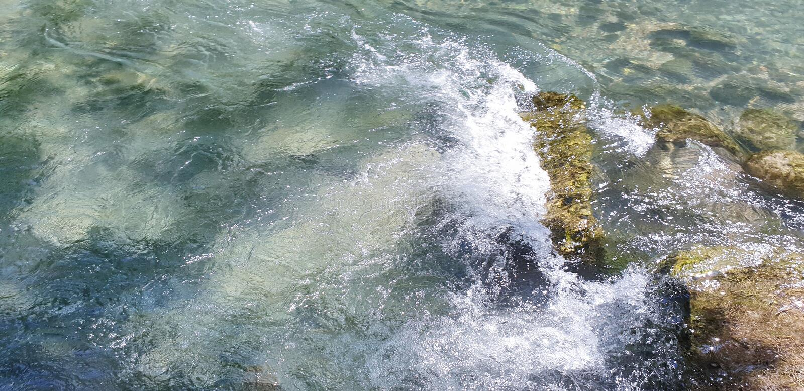Waves in water crashing on stones stock photo