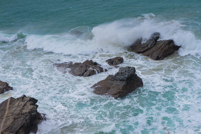 Waves on cornish rocky cliff stock image