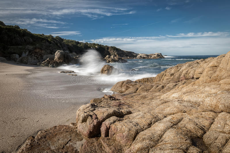 Waves crash onto a small sandy cove near Calvi in Corsica. Waves crashing onto rocks and a golden sandy beach at a small cove near Lumio in the Balagne region of royalty free stock image