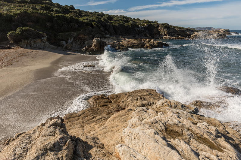 Waves crash onto a small sandy cove near Calvi in Corsica. Waves crashing onto rocks and a golden sandy beach at a small cove near Lumio in the Balagne region of royalty free stock images